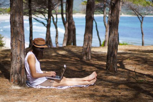 Freelance woman working in vacation on the laptop sitting in a pine forest on the sea, smart working lifestyle concept theme and life choice