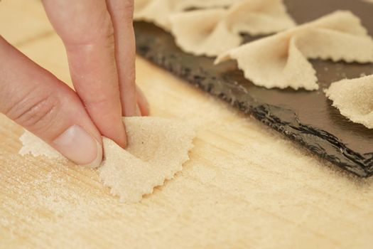 Close up detail of process of homemade vegan farfalle pasta with durum wheat flour. The cook kneads the dough on the wooden cutting board, traditional Italian pasta, the woman cooks the food