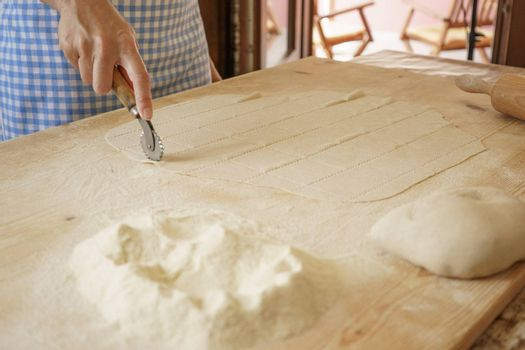 Close up process of homemade vegan farfalle pasta with durum wheat flour. The cook uses the rolling cutter to cut the dough, traditional Italian pasta, the woman cooks the food in the kitchen