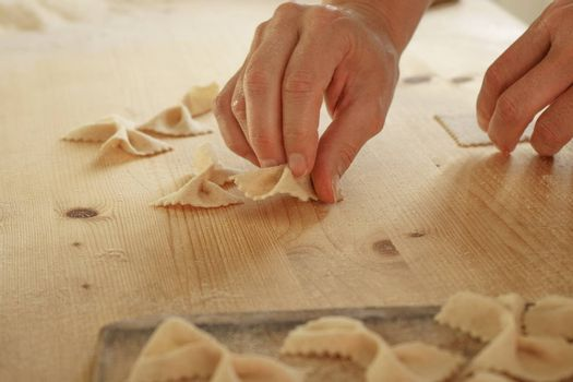 Close up process of homemade vegan farfalle pasta with durum wheat flour. The cook shapes the dough on the wooden cutting board, traditional Italian pasta, the woman cooks the food in the kitchen