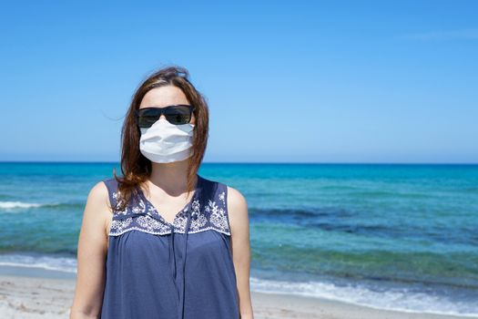 Coronavirus seaside holidays: a woman standing on the sand at the beach looking at the sun with the mask for Covid-19 pandemic