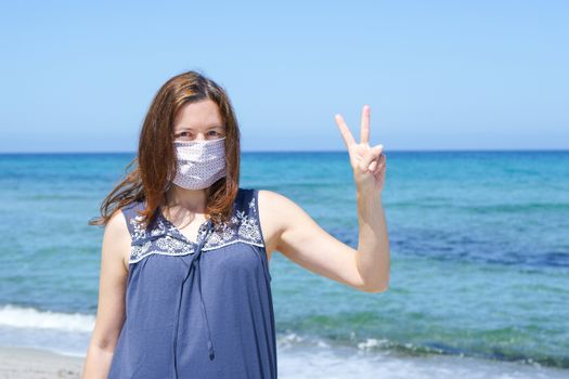 Coronavirus seaside holidays: a woman standing on the sand at the beach looking at the camera with fingers in victory and the mask for Covid-19 pandemic