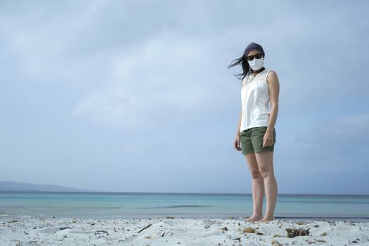 Coronavirus seaside holidays: shot of a woman at the beach look at the camera with the mask for Covid-19 pandemic with cloudy sky