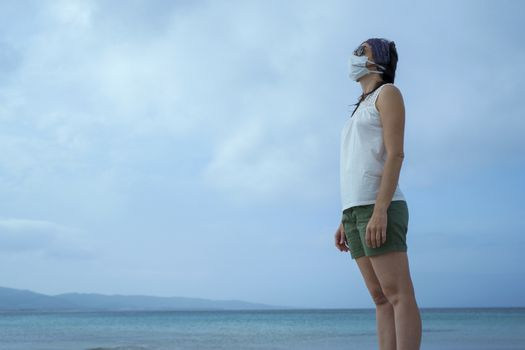 Coronavirus seaside holidays: shot of a woman at the beach looking at the sun with the mask for Covid-19 pandemic with cloudy sky