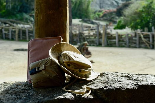 Symbols of travel - an old cowboy had and a weathered travel bag; natural background and man-made objects