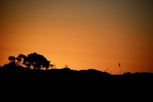 A Flagstick at a Golf Course; beautiful sunset colours and a silhouette of the golf flagstick against the evening sky.