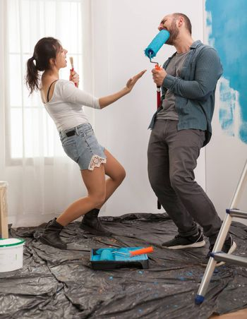 Funny couple decorating living room and sing on renovation tools. Apartment redecoration and home construction while renovating and improving. Repair and decorating