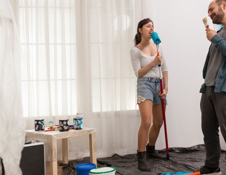 Two lovers singing together on renovation tools while painting the wall. Apartment redecoration and home construction while renovating and improving. Repair and decorating.