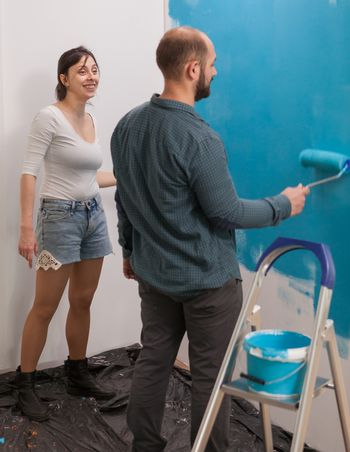 Happy girlfriend renovating the flat with her husband. Home during renovation, decoration and painting. Interior apartment improvement maintenance. Roller, ladder for house repair