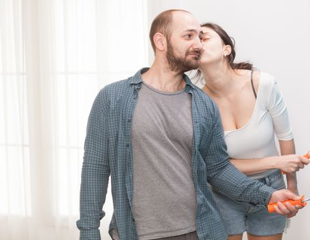 Inlove wife kissing her husband during home renovation. Apartment redecoration and home construction while renovating and improving. Repair and decorating.