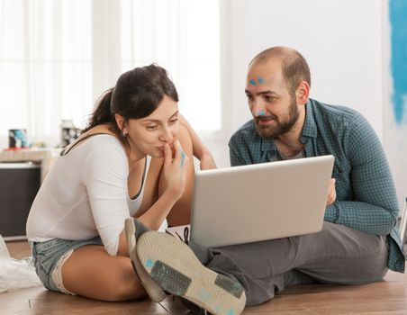 Married couple buying furniture online for their new apartment. Apartment redecoration and home construction while renovating and improving. Repair and decorating.