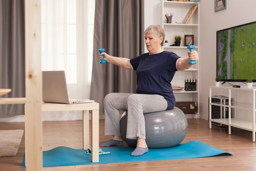 Retired woman training shoulders with weights. Old person pensioner online internet exercise training at home sport activity with dumbbell, resistance band, swiss ball at elderly retirement age