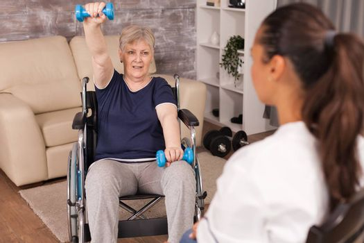 Immobilized senior woman doing shoulder exercises assisted by nurse. Disabled handicapped old person recovering professional help nurse, nursing retirement home treatment and rehabilitation