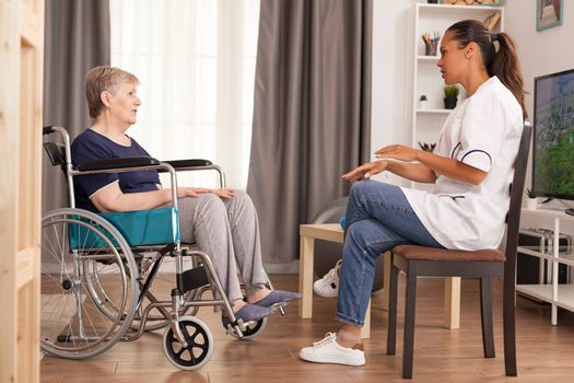 Nurse checking on retired handicapped old woman. Disabled handicapped old person recovering professional help nurse, nursing retirement home treatment and rehabilitation