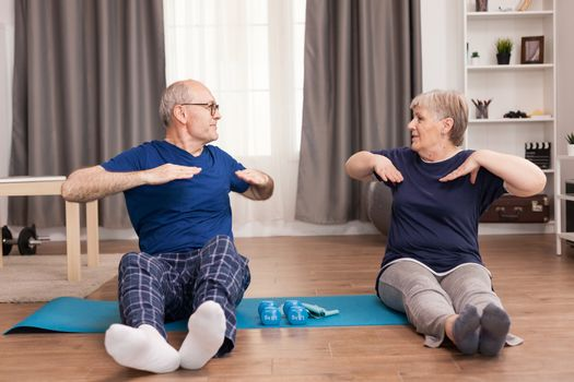 Modern old couple practicing sport together in their apartment. Old person healthy lifestyle exercise at home, workout and training, sport activity at home on yoga mat.
