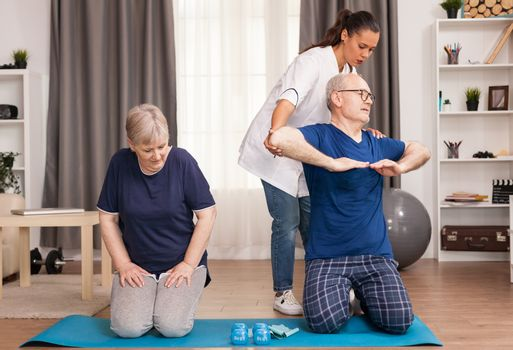 The therapist helping the old man while his wife relaxes. Home assistance, physiotherapy, healthy lifestyle for senior old person, training and recovery with professional physiotherapist