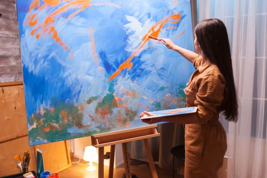 Artist holding paint palette in art workshop. Painting on large canvas. Modern artwork paint on canvas, creative, contemporary and successful fine art artist drawing masterpiece
