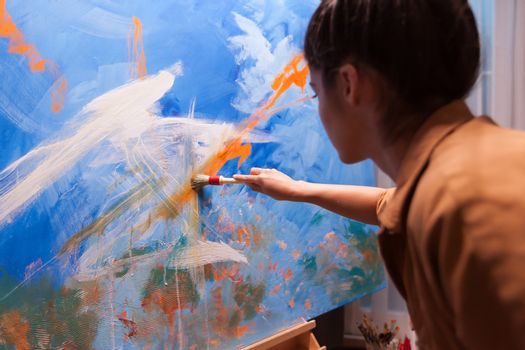 Woman working on details on large canvas in art studio. Modern artwork paint on canvas, creative, contemporary and successful fine art artist drawing masterpiece