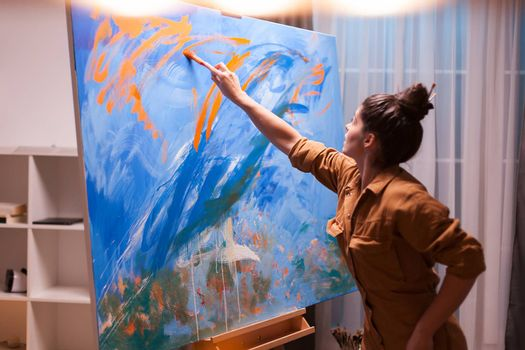 Painting with oil paint in art studio on large canvas. Modern artwork paint on canvas, creative, contemporary and successful fine art artist drawing masterpiece