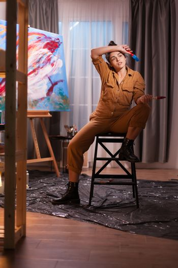 Overworked artist in studio sitting on chair holding paint brush. Modern artwork paint on canvas, creative, contemporary and successful fine art artist drawing masterpiece