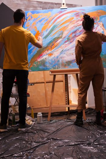 Couple of artist painting together in art workshop. Modern artwork paint on canvas, creative, contemporary and successful fine art artist drawing masterpiece