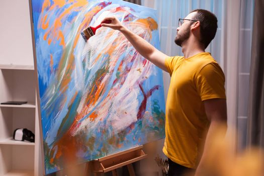 Man painting a masterpiece on large canvas in art studio. Modern artwork paint on canvas, creative, contemporary and successful fine art artist drawing masterpiece