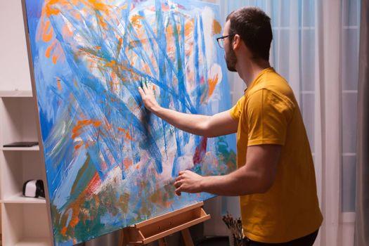 Relaxing painting on canvas with fingertips in art studio. Modern artwork paint on canvas, creative, contemporary and successful fine art artist drawing masterpiece