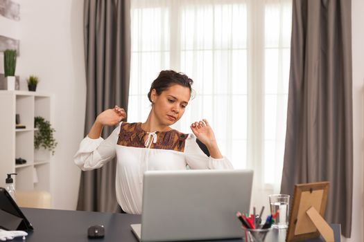 Entrepreneur stretching her back while working on laptop from home office.