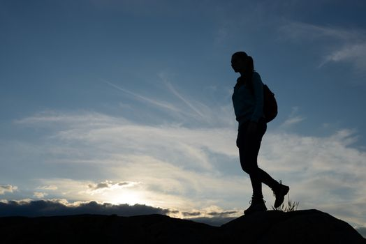 Young Woman Traveler Hiking with Backpack on the Beautiful Rocky Trail at Warm Summer Sunset. Travel and Adventure Concept.