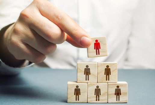 A hand places a mentor leader at the head of a group of people. Team building, hierarchical power vertical. Leadership skills. Teamwork, cooperation and collaboration. Management of effective team.