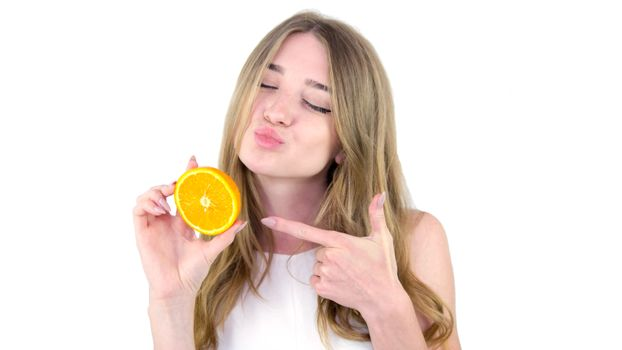 Girl with juicy fruit,on a white background,close-up,beautiful and young girl in a white dress with an orange in her hand.