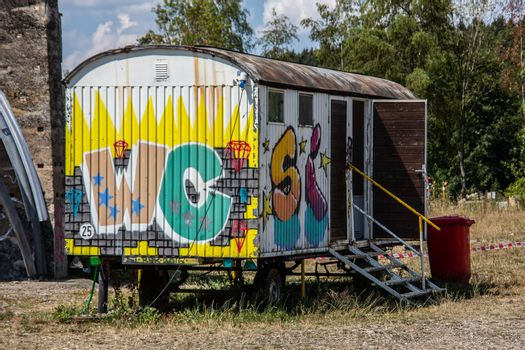 colorful painted construction site trolleys as toilets