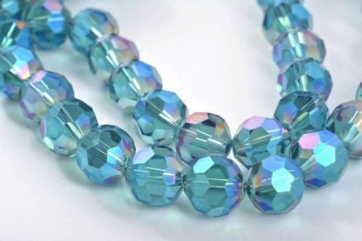 Beautiful Light Blue Glass Sparkle Crystal Isoalted Beads on white background. Use for diy beaded jewelry. Space for text
