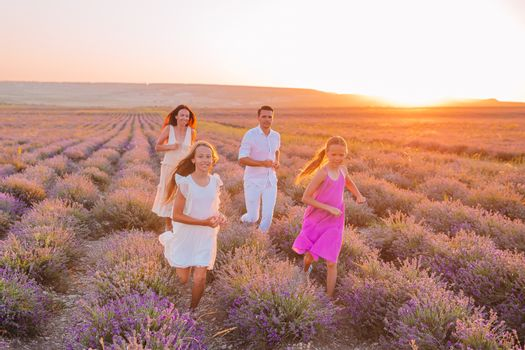 Beautiful young family having fun on purple flower lavender field