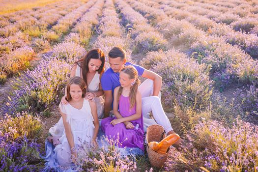 Beautiful young family on picnic on purple flower lavender field