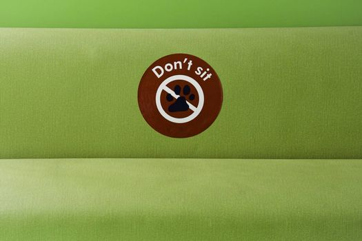 A green padding seating area with a Don't Sit sign, as part of the safety social distancing measures put in place to combat the global Covid 19 pandemic