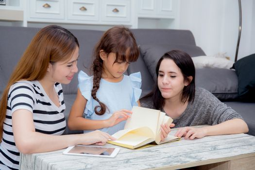 happy family mother, aunt, freind and daughter teaching read a book at home.