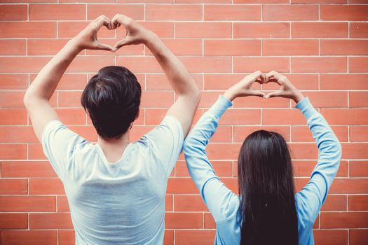Young asian couple happy in love with gesture hand heart shape on brick background.