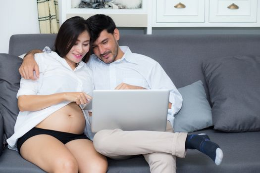 Portrait of a asian young couple husband and wife sitting on the sofa while using notebook computer in living room.