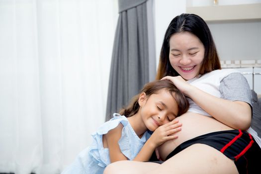 Little child listening baby in belly and hug mother with happiness in room.
