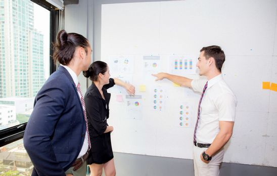 three business people in modern office looking report and analyzing with talking in meeting room.