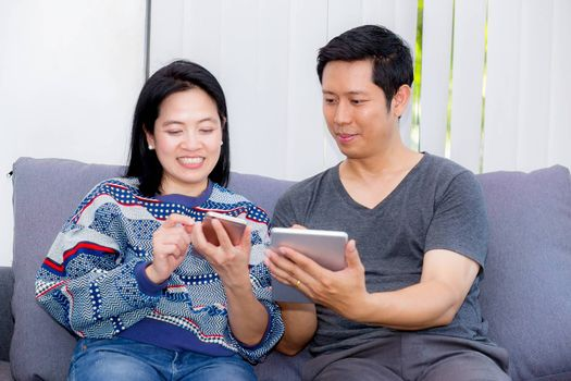 Two friends on line with multiple devices and talking sitting on a sofa in the living room in a house interior, communication concept.