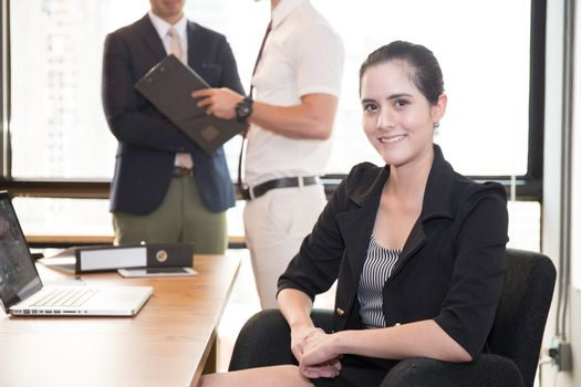 American business woman sitting with people in at modern meeting room.