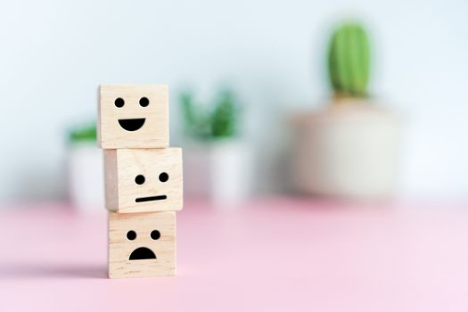 Smile face and cart icon on wood cube. Optimistic person or people feeling inside and service rating when shopping, satisfaction concept in business.