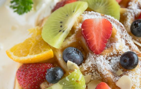 Strawberry Blueberry Kiwi Lemon Waffle Whipped Cream Dessert Close Up. Fruity dessert food and drink category