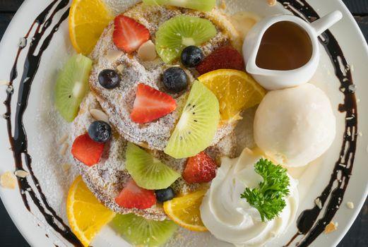 Flatlay Strawberry Blueberry Kiwi Lemon Waffle Whipped Cream Ice Cream Chocolate and Syrup Dessert. Fruity dessert food and drink category