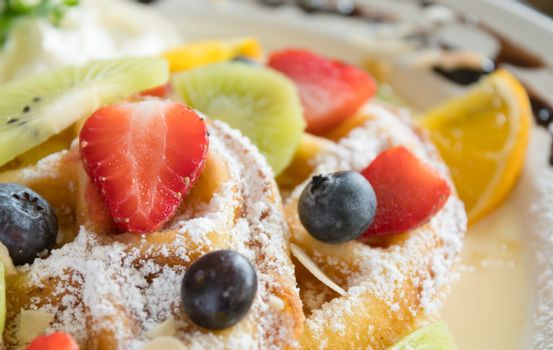 Strawberry Blueberry Kiwi Lemon Waffle Dessert Close Up. Fruity dessert food and drink category