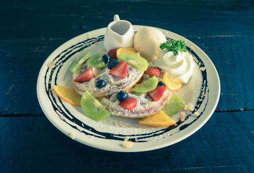 Vintage Strawberry Blueberry Kiwi Lemon Waffle Whipped Cream Ice Cream Chocolate and Syrup Dessert. Fruity dessert food and drink category