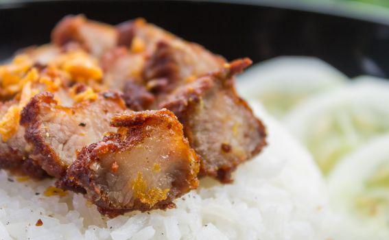 Thai Food Fried Pork with Garlic and Cucumber in Black Dish. Fried pork with garlic or steak on rice and cucumber in food and drink category