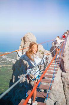 Girls crossing the chasm on the rope bridge. Black sea background, Crimea